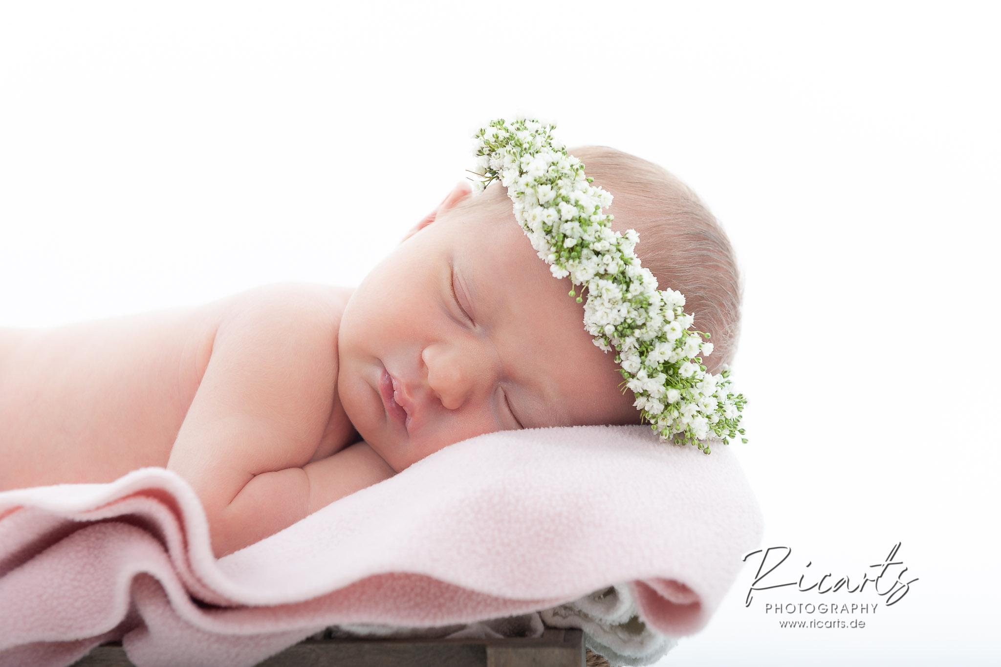 Baby-Newborn mit Blumenhaarkranz