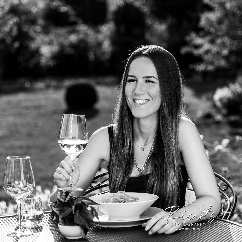 Junge Frau am Tisch mit Spaghetti-Teller und Glas, outdoor