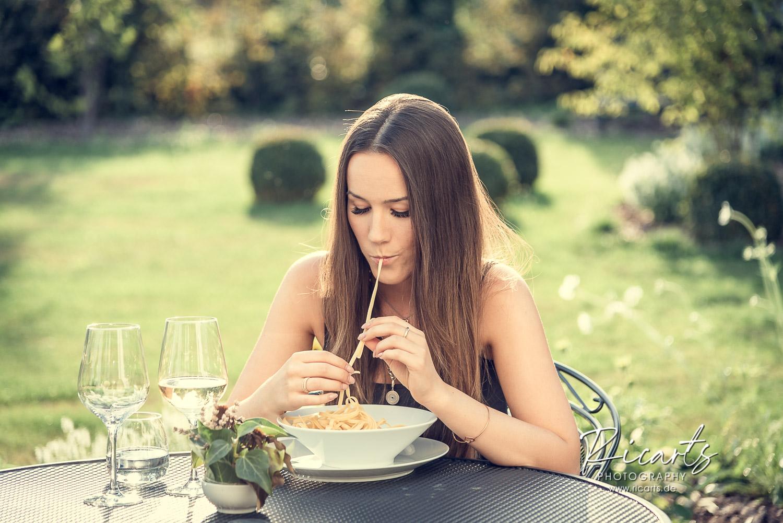 Junge Frau isst Spaghetti, outdoor