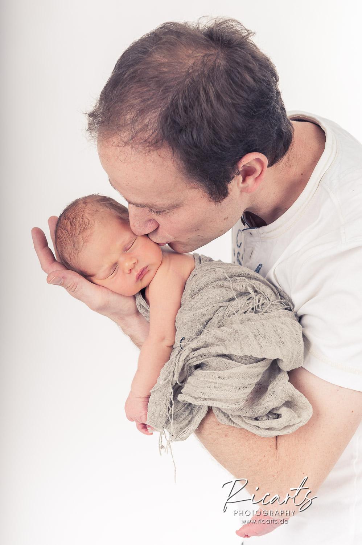 Mann mit Newborn Baby schlafend