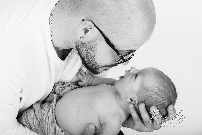 Mann mit Newbornbaby im Arm
